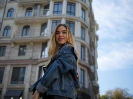 Atractiva chica rubia sonriendo en el fondo de un edificio moderno foto
