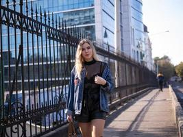 cute blonde with flowing hair in a denim jacket on the bridge outdoor photo