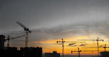 Building Construction With Cranes During Sunset. Cranes Building photo