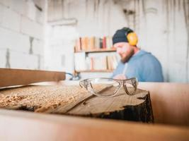 Gafas de seguridad de carpintero en tocón de madera. taller de carpinteria foto