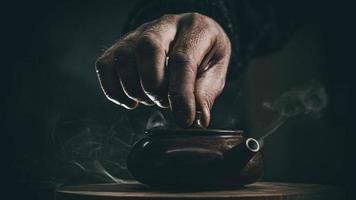 Close-up mano masculina cerró la tapa de una tetera de arcilla hecha de arcilla yixing foto