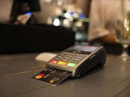 close up payment machine on the table for paying bill by at table photo