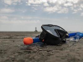 Máscara de buceo negra y snorkel en un muelle de hormigón foto