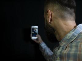 hombre con barba y bigote mira en el teléfono y hace una selfie foto
