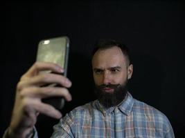 Hombre elegante con barba y bigote hace selfie en el teléfono foto