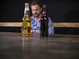 dos botellas de cerveza están de pie sobre la mesa foto