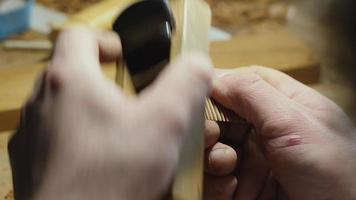 artisan processes a wooden comb with a planer video