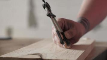 A carpenter marks a pine wooden plank with a compass video