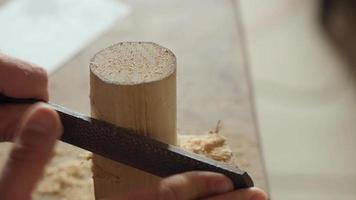 craftsman processes a piece of wood with a file video