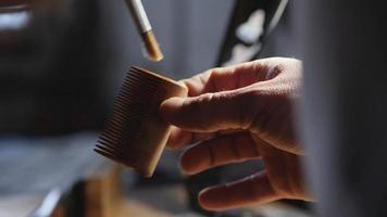 artisan applies wood impregnation to wooden beard comb video