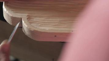 woodcarver cuts edges on a wood product with a knife video