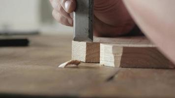wood carver cuts the edges of a wood board with a flat chisel video