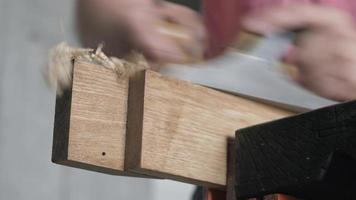 woodworker planes a wooden oak plank with a hand plane video