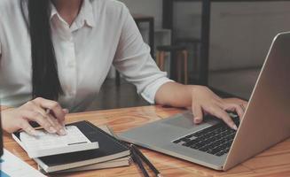 Cerrar empresaria usando calculadora y portátil foto