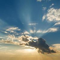 Beautiful blue sky with clouds and sun rays photo