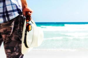 Close up tourist holding straw hat and sunglasses photo