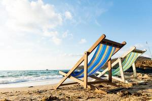 Summer vacation deckchairs on tropical beach photo