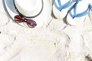 Close up straw hat, flip-flops and sunglasses photo