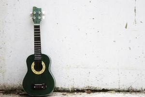 A green ukulele leaning against white wall photo