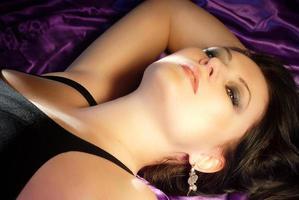 Retrato de mujer de belleza sensual en la cama de seda púrpura foto