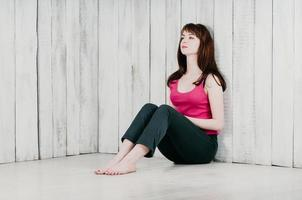 a pretty girl in a pink top, sitting on the floor, leaning on wall photo