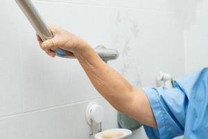Asian senior woman patient use toilet handle security photo