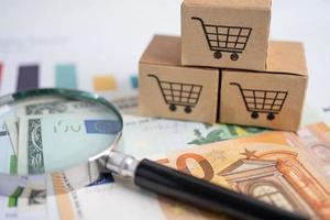 Shopping cart logo on box with magnifying glass and Euro banknotes. photo
