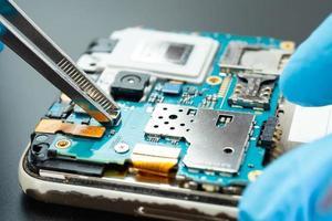 técnico que repara el interior del disco duro con un soldador. foto