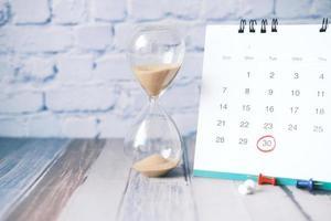 Reloj de arena que fluye a través de la bombilla de reloj de arena y calendario en la mesa foto