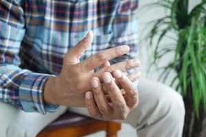 man suffering pain in finger while sited photo