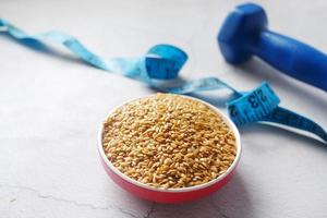 flax seeds, measurement tape and dumbbell on table , photo