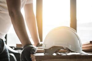 Centrarse en el casco de seguridad en la mesa de trabajo y carpintero foto