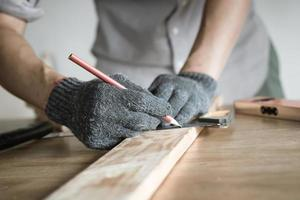 carpenter measuring and writing on wood with copy space background photo