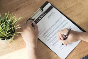 Businessman signing on contract paper on table photo