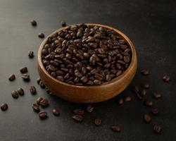 Coffee beans in wooden bowl on grunge background photo