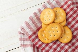 Galletas cracker con mantel sobre fondo de mesa de madera blanca foto