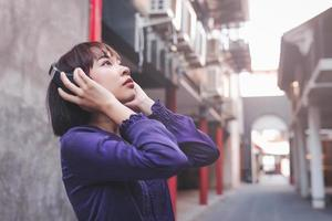 Happy young asian woman listening to music with headphones photo