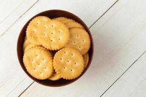 Galletas cracker redondeadas en un recipiente de madera sobre la mesa de madera blanca foto