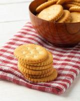 Galletas cracker redondeadas en un cuenco de madera con mantel foto