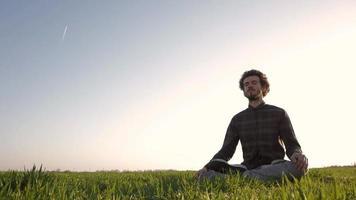 jovem relaxando e meditando no campo video