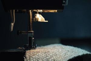 una máquina de coser cose tela de arpillera. coser ropa de tela de cáñamo foto