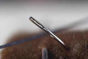 Primer plano de la aguja de coser en una bola de hilo foto