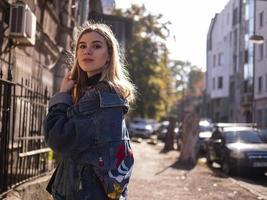 Hermosa chica rubia se encuentra en un antiguo callejón con una chaqueta de mezclilla foto