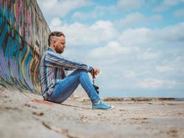Hombre hipster barbudo con cresta se sienta en un muelle de hormigón foto