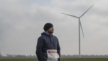 Hombre de pie en un campo con el telón de fondo de los molinos de viento foto