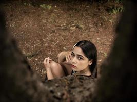 atractiva chica de apariencia caucásica sentada cerca de un árbol, foto