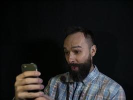 hombre con barba y bigote mira en un teléfono móvil foto