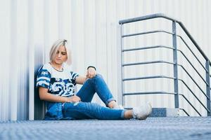 Beautiful girl with short white hair dressed in jeans in urban style photo