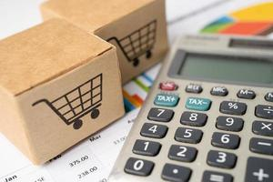 Shopping cart logo on box with calculator on graph photo