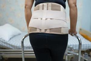 Señora asiática paciente vistiendo cinturón de soporte para el dolor de espalda foto